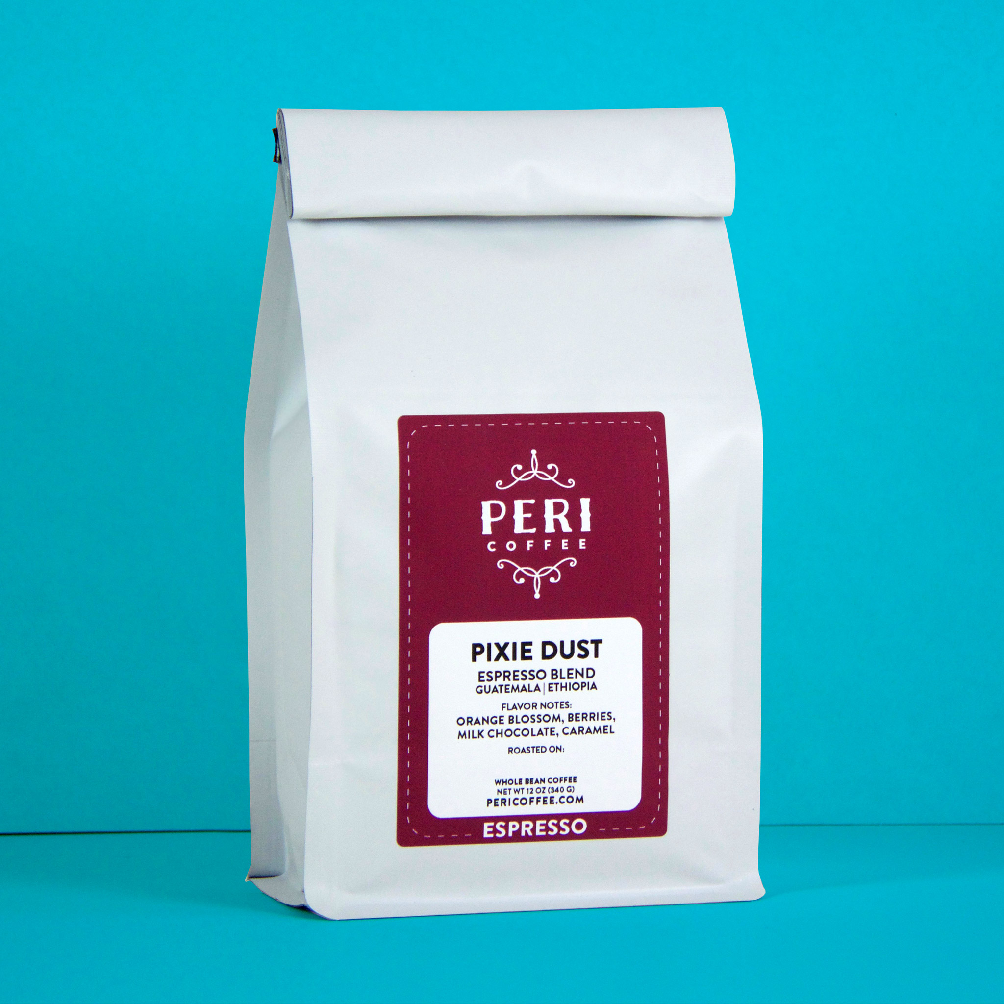 White bag of coffee with a maroon label in front of aqua blue background.